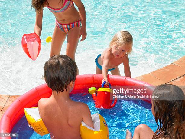 four children playing in a kiddie pool near a backyard pool. - saint ferme stock pictures, royalty-free photos & images