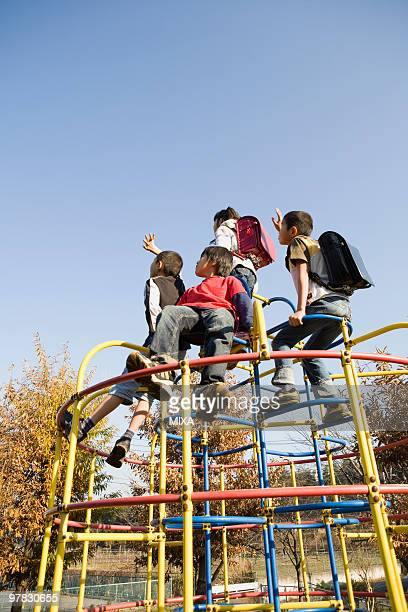 Four children playing on jungle gym