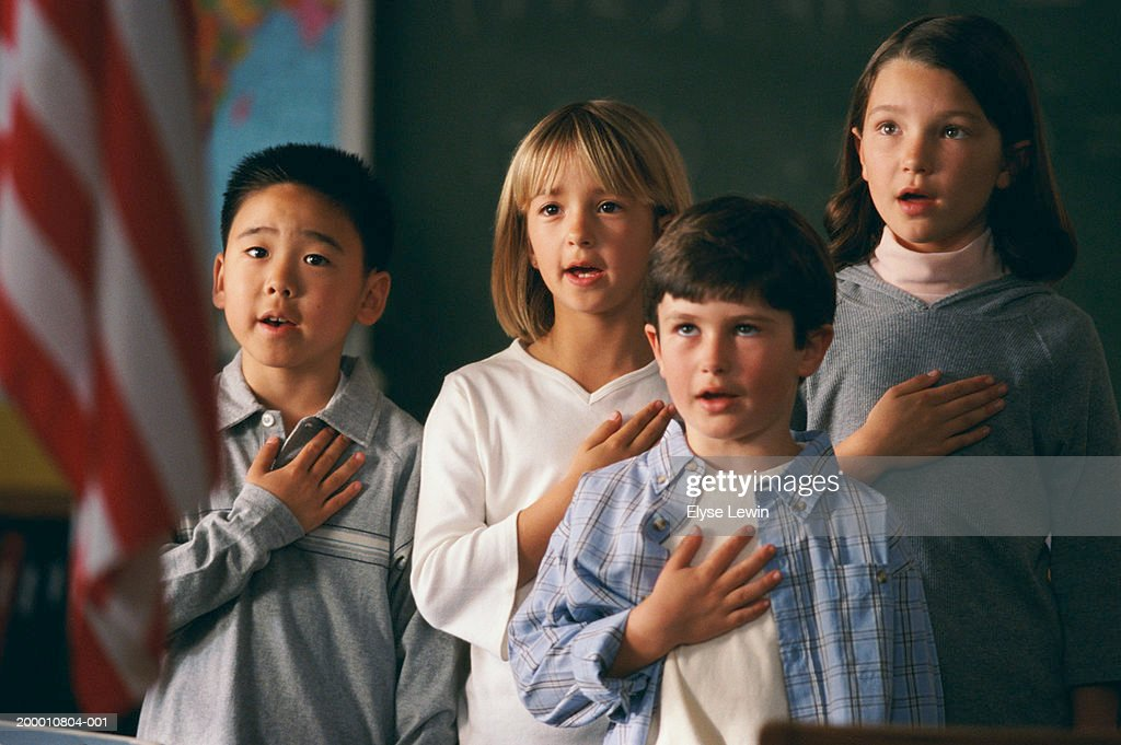 Four children (5-9 years) reciting pledge of allegiance to US flag : Stock Photo