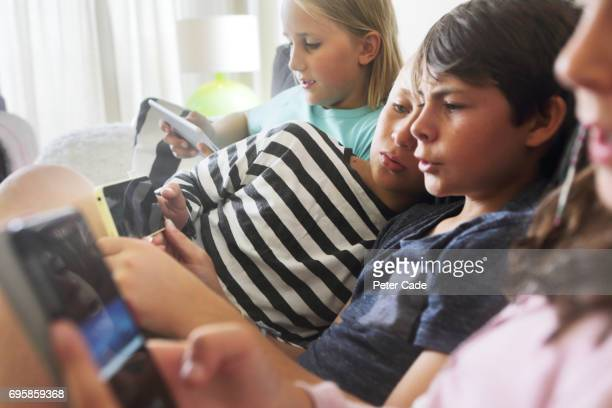 Four children sat on sofa looking at phones and tablets