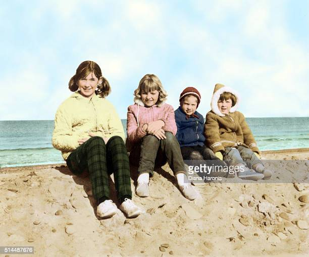 four children sitting on a sand dune at the beach - archival photos stock pictures, royalty-free photos & images