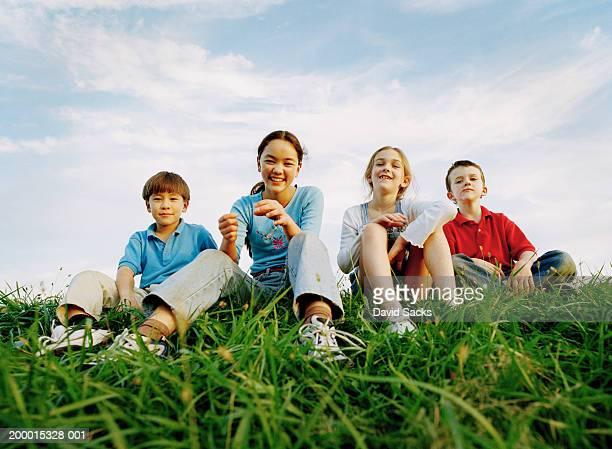 Four children sitting on grass, smiling, portrait