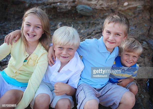 Four children sitting on rocks hugging