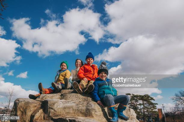 Four children sitting on the top of a climbing rock at a playground