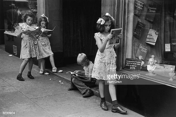 Four children three girls and one boy loiter on a sidewalk by a store display window while reading comic books New York City