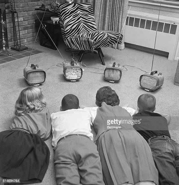 Four children watch four different small televisions on a living room floor.