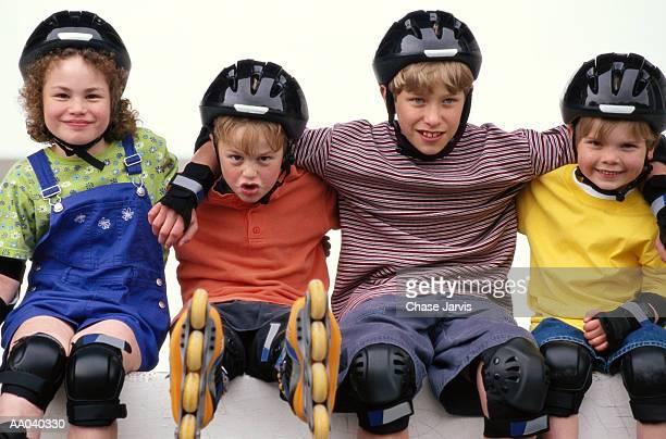 Four children (4-8) wearing inline skates, portrait