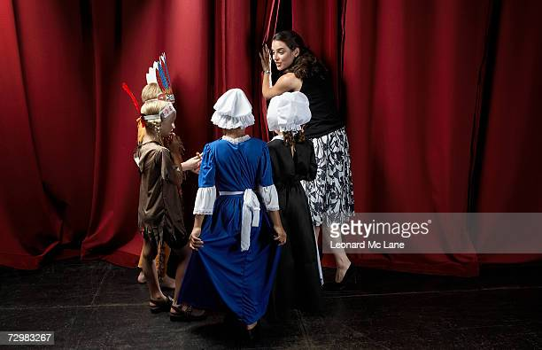 Four children (7-9) with teacher waiting behind theatre curtains