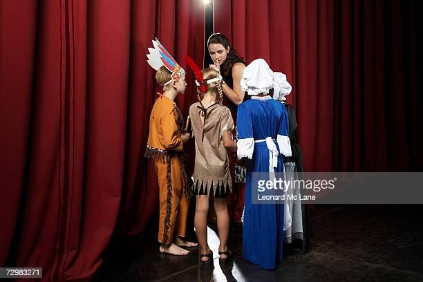 Quatre enfants (7 à 9) et enseignant attend derrière les rideaux de théâtre