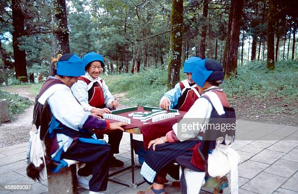 four chinese women playing mahjong. - mahjong stock photos and pictures