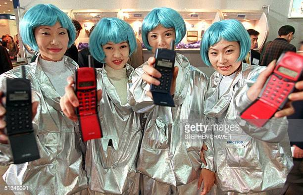 Four Chinese women wearing blue wigs display their company's latest mobile phones 27 October during China's international telecommuncations...