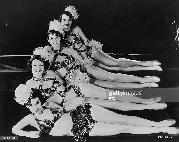 Four chorus girls wearing sparkly costumes recline in a row circa 1935
