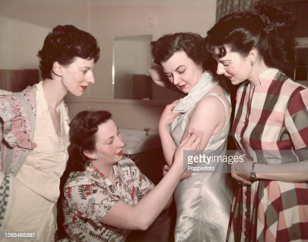 Four civilian women volunteers check their vaccination marks at a Navy Army and Air Force Institutes reception centre in Woking England prior to be...