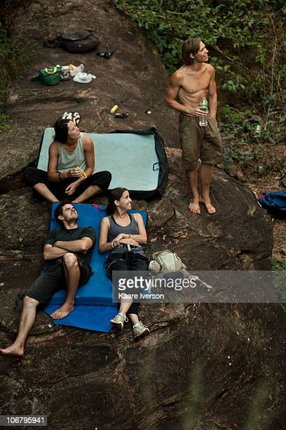 four climbers lounging on crashpads and watching something out of frame. - out of frame stock pictures, royalty-free photos & images