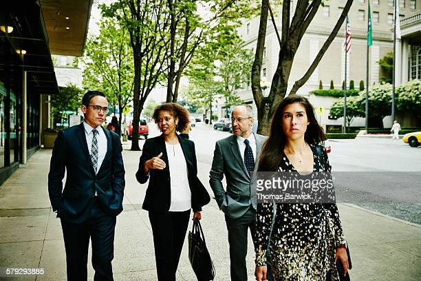 Four colleagues in discussion walking on sidewalk
