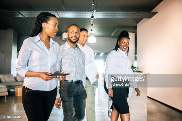 four colleagues walking through office reception - western cape province stock pictures, royalty-free photos & images