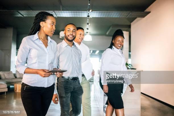 Vier Kollegen zu Fuß durch Büro Empfang