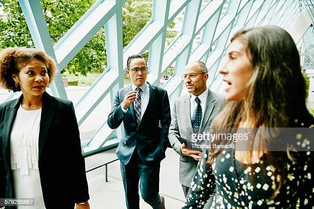 Four colleagues walking through outdoor corridor