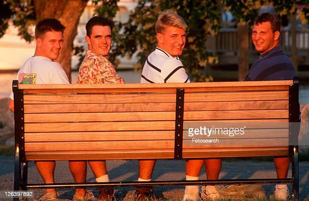 four college aged men on a park bench - only men stockfoto's en -beelden