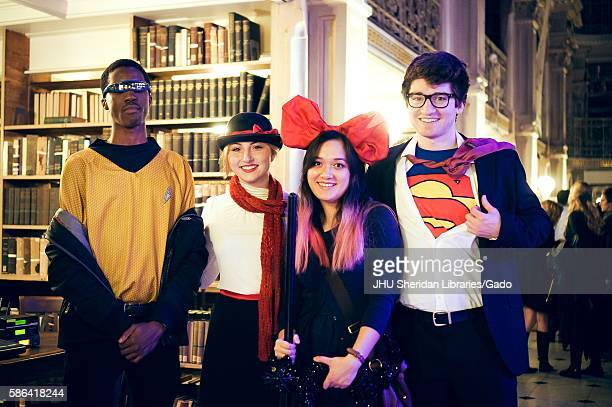 Four college students are in costume and are posing the boy on the far right is dressed as Superman and the girl next to him is wearing a large red...