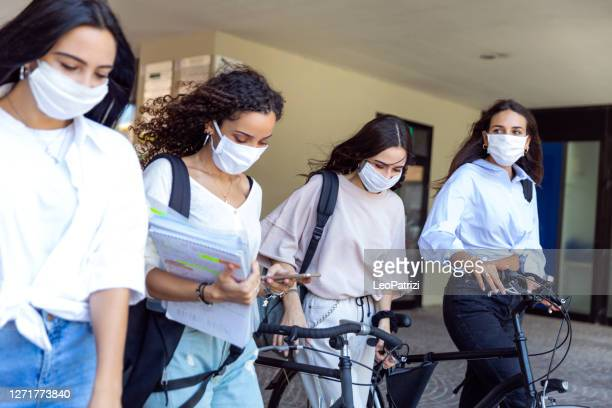 vier studenten die in de straat lopen - vier personen stockfoto's en -beelden