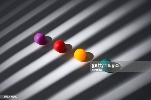 four colored spheres on striped light and shadow - small group of objects stock pictures, royalty-free photos & images