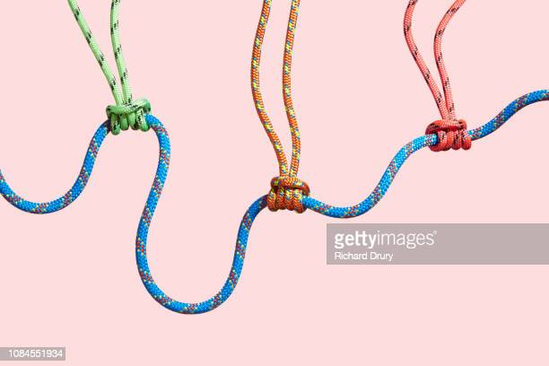 four coloured ropes supporting a larger rope - soporte conceptos fotografías e imágenes de stock