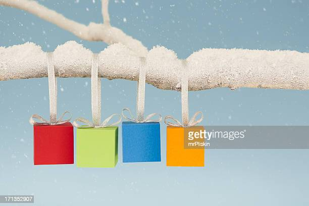 four colourful christmas gift boxes hanging from snow covered branch - four objects stock pictures, royalty-free photos & images