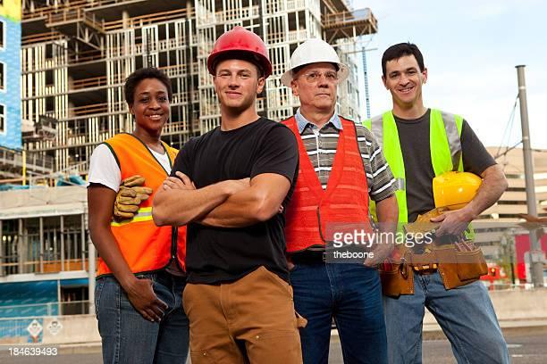 Cuatro trabajadores de la construcción de pie frente de un edificio del hotel.