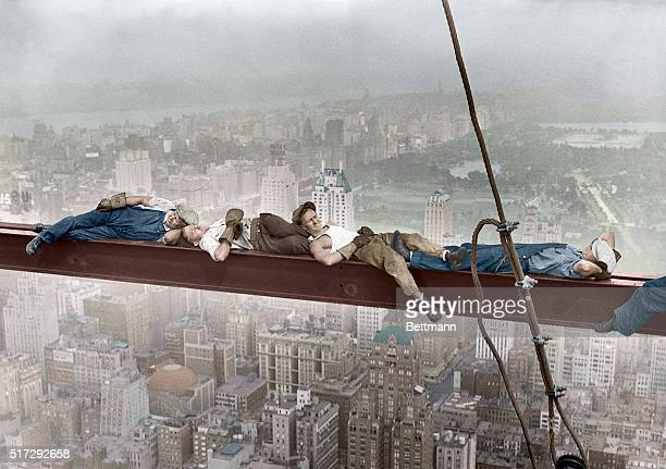 Four construction workers take a nap balanced on a steel girder hung 800 feet over Manhattan during the construction of the RCA Building Man on left...