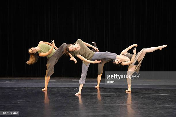 Four contemporary dancers kicking while performing on stage