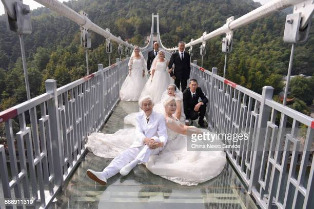 Four couples in wedding dress attire pose for a photo in celebration of their golden wedding anniversary on a transparent glass bridge on October 26...