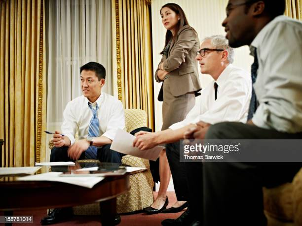 Four coworkers discussing project in hotel room