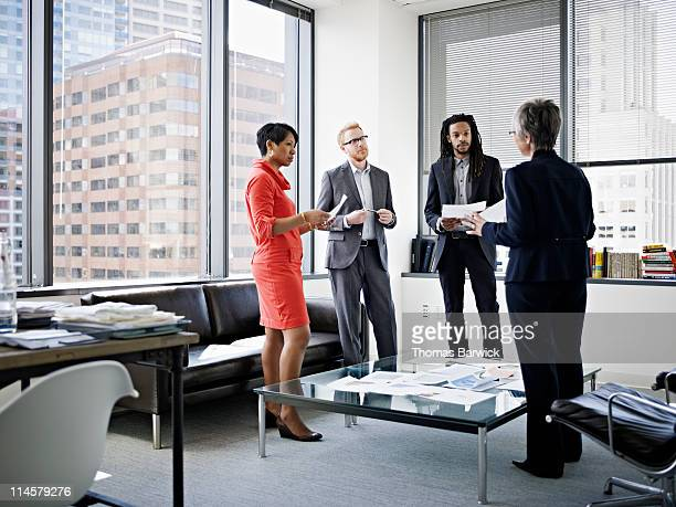 Four coworkers in corner office in discussion