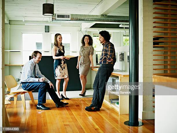 Four coworkers in discussion in office lobby