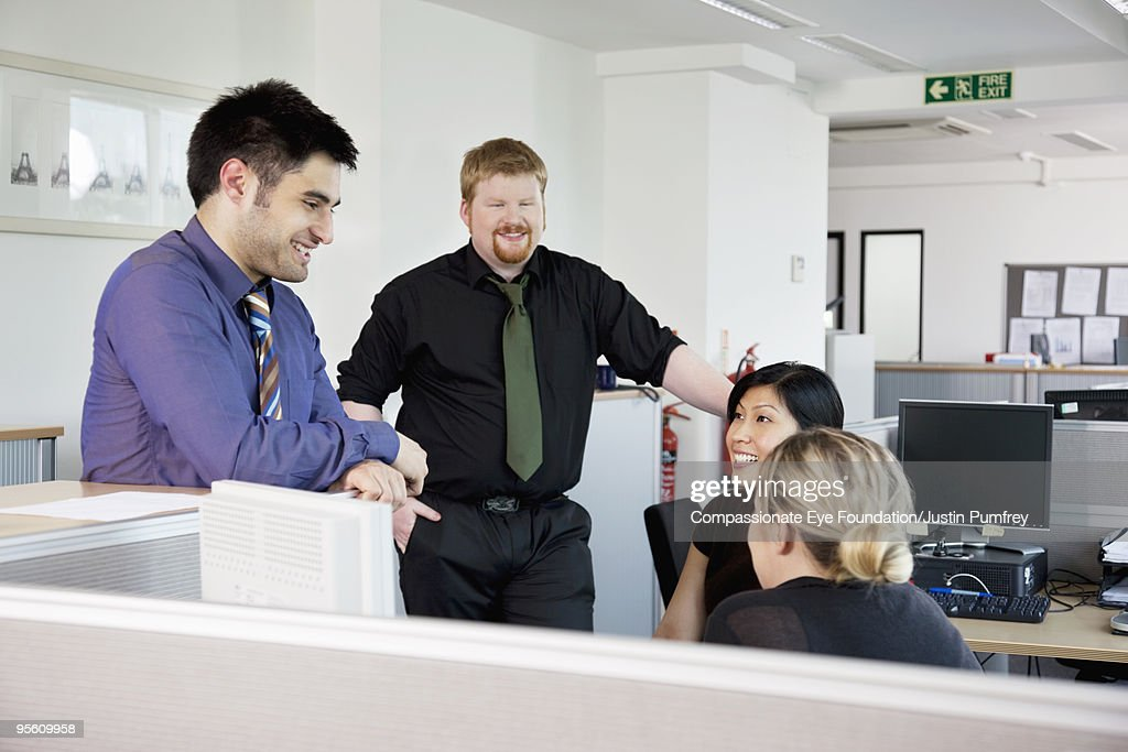 Four coworkers talking in a cubicle : Stock Photo