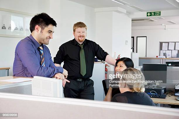 Four coworkers talking in a cubicle