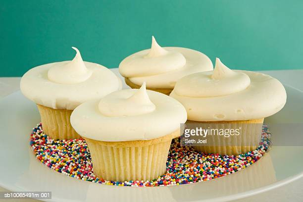 Four cupcakes on plate with multicoloured sprinkles