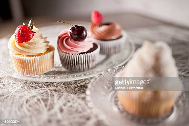 Four cupcakes with a cherry and a strawberry a raspberry on a plate on July 15 2015 in Berlin Germany