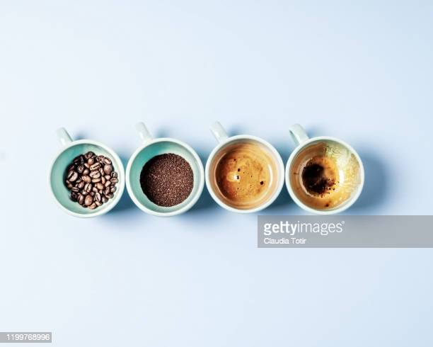 four cups of coffee on blue background - café moulu photos et images de collection