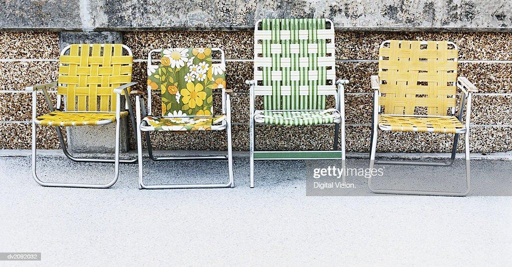 Four Deckchairs in a Row Against a Wall : Stock Photo