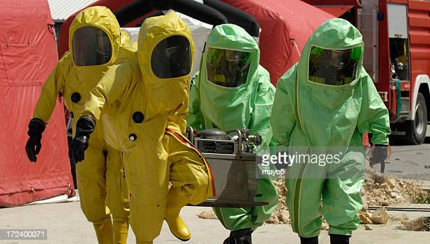 Four decontamination operatives at work in green and yellow