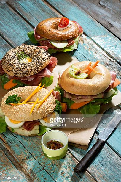 Four different bagels garnished with salami, slices of bacon, rocket salad, tomato, lettuce, cucumber carrot, egg, cream cheese and cress and parsley