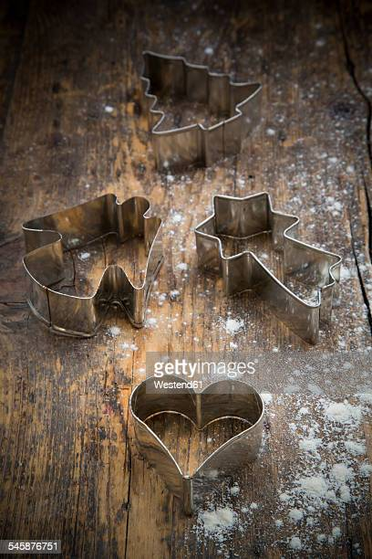 Four different cookie cutters and scattered flour on dark wood