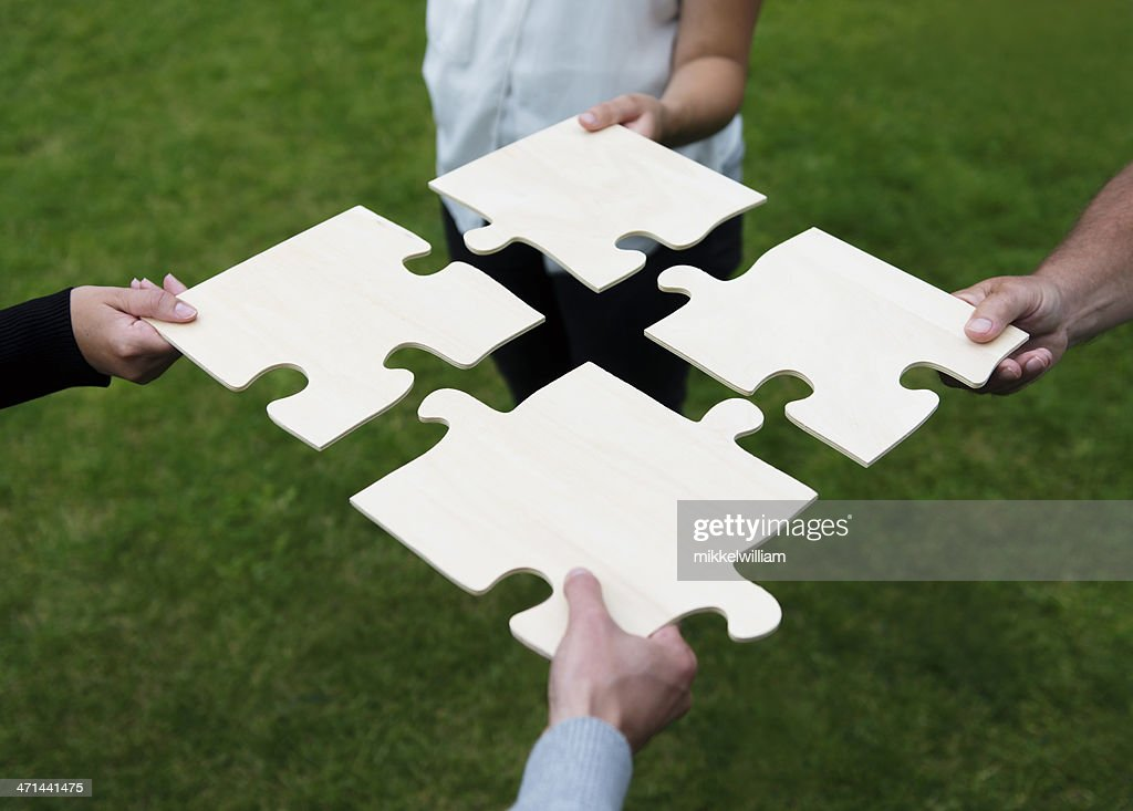 Four different people connecting large puzzle pieces : Stockfoto