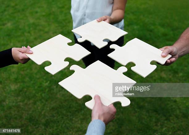 four different people connecting large puzzle pieces - vier personen stockfoto's en -beelden