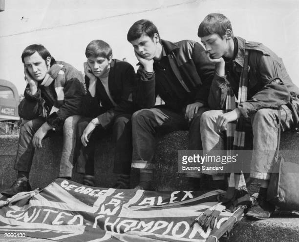Four disappointed Manchester United football supporters sitting outside Wembley Stadium London unable to buy tickets for the European Cup Final...