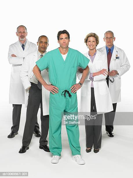 Four doctors and surgeon standing on white background, portrait