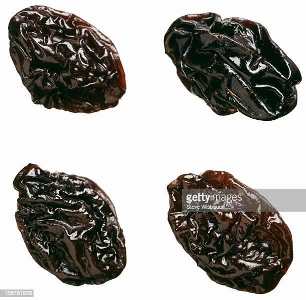 four dried plums or prunes - dörrpflaume stock-fotos und bilder