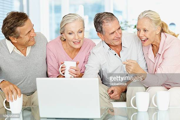 Four elderly friends sitting together and looking at laptop
